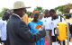 President Yoweri Museveni handing over an MTN Mobile Money card to a beneficiall