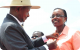 Miss Maria Odido receiving a Crested Crane Medal from President Museveni for bei
