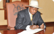 President Museveni signing in Parliament visitors book
