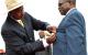 Minister Muruli Mukasa receiving a medal while KamandaBataringaya waits for his